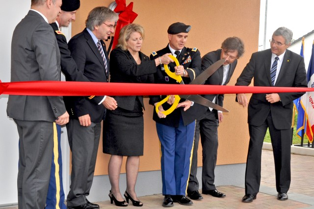 Col. David Carstens, U.S. Army Garrison Wiesbaden commander, is joined by Wiesbaden Lord Mayor Helmut Mueller, Installation Management Command-Europe Director Kathleen Marin and other military and civilian officials in cutting the ribbon to officially open the new Newman Village housing area in Germany.