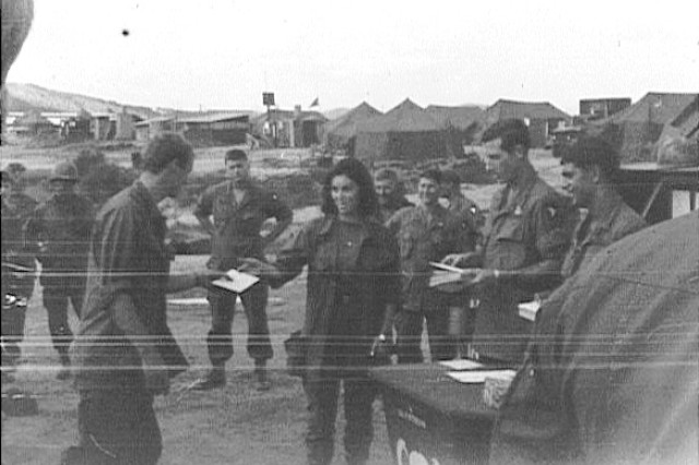 "This was Linda Patterson's visit to Vietnam during Christmas 1968 where she met fellow Soldiers of her brother Joe who was killed in action while with the 101st Airborne Division. The Christmas cards she's handing out to the Soldiers contains the San Mateo, Calif., ""gift,"" a medallion some still carry to this day."