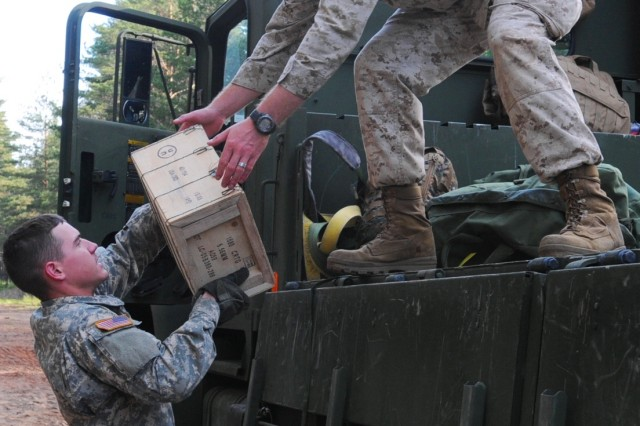 Pfc. Matthew Curran, an ammunition specialist with 23rd Ordnance Company, 18th Combat Sustainment Support Battalion, and a Pensacola, Fla., native, passes a case of ammunition to a Marine during an ammunition distribution on the Camp Adazi training grounds in Latvia June 15. (Photo by Staff Sgt. Michael J. Taylor, 21st TSC Public Affairs)