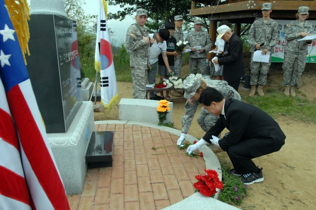 Col. Kathleen A. Gavle, United Stated Army Garrison-Daegu commander, and a South Korean official, honor the fallen during the Hill 303 Wreath Laying and Memorial Ceremony at the top of the Hill 303 near Camp Carroll in Waegwan, South Korea, June 15, 2012. Hill 303 was a major battle site during the Korean War where Soldiers of the U.S. 1st Cavalry Division sacrificed their lives in the successful defense of Waegwan.