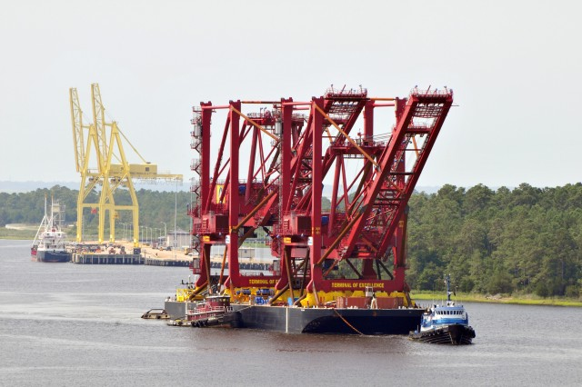 The two new ship-to-shore container gantry cranes make their way up the Cape Fear River and pass the current smaller cranes at Military Surface Deployment and Distribution Command's Military Ocean Terminal Sunny Point, Southport, N.C.  The two new cranes will  give MOTSU greater speed and efficiencies of vessel operations for munitions movements.