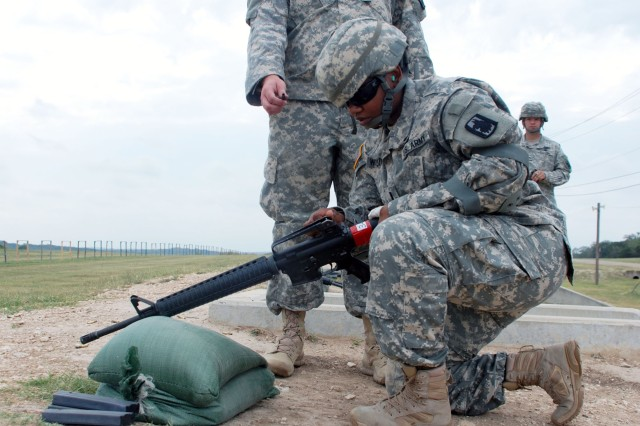 A Soldier of the 338th Military Intelligence Battalion receives some advice in adjusting her M16 for qualification on the firing range on Camp Bullis June 8. The U.S. Army Reserve Battalion, most of whose Soldiers reside in Kansas or New York State, came together for annual training. (U.S. Army photo by Gregory Ripps)