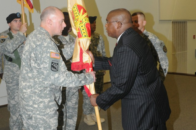 James Abney, Installation Management Command G-9 Family and MWR Programs director, Fort Sam Houston,^Texas, hands the Fort Leonard Wood IMCOM colors to incoming Garrison Commander, Col. William Pfeffer, during a ceremony in Nutter Fieldhouse on Friday. Col.^Charles Williams relinquished command during the ceremony.
