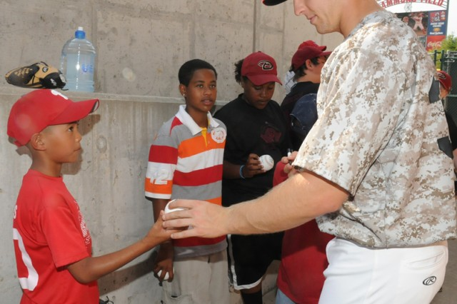 Springfield Cardinals outfielder Kyle Conley signs a baseball for Rovic Denuna, 12, a member of a Fort Leonard Wood youth sports team, before the Springfield Cardinals' annual Fort Leonard Wood Military Appreciation Day game in Springfield, Mo., June 16, 2012.