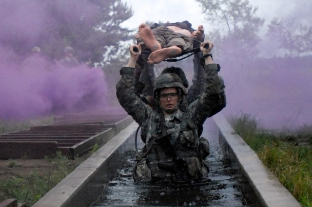 Sgt. Alexandria V. Davenport carries a simulated casualty on a litter through a water obstacle during the Mountain Medic Expert Field Medical Badge testing lanes. The EFMB testing was held June 11-15 at the Bridgewater-Vaccaro Medical Simulation Training Center Area here.