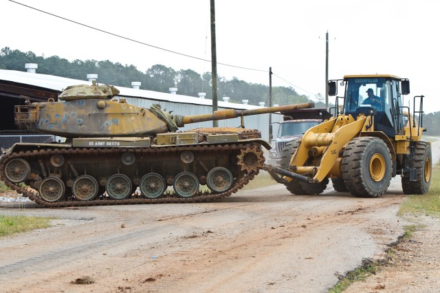 Paul Griffin of Anniston Army Depot's Directorate of Public Works moves a tank from the fence line near the Lake Yard Interchange construction site to its new storage area.