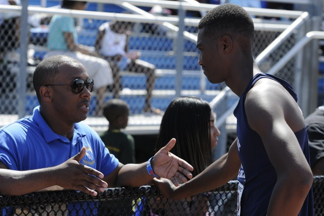 Fort Meade Highsteppers Track and Field coach Cliff Timpson talks with Trevon Edwards, 16, before his long jump event at last week's four-day meet at Prince George's County Sports and Learning Complex. Team members and coaches are preparing for the Junior Olympics as 13 young athletes will compete for national titles. (Photo by Staff Sgt. Kyle Richardson)
