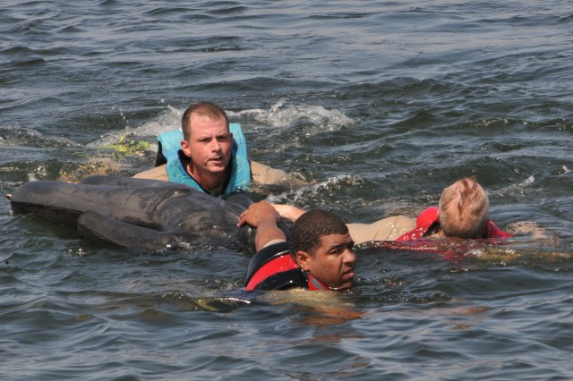 "Capt. Brandon Fridia, Lt. Col. Gavin Gardner and Maj. John Scarbrough from 100th Brigade Support Battalion, swim with a dummy that weights 80-100 pounds across Lake Elmer Thomas at Fort Sill, Okla., during the Red Dragon ""Endurathon,"" June 2, 2012."