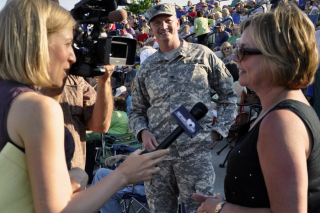 Not to be outdone by her husband, the Watervliet Arsenal's commander, Barbara Migaleddi takes a moment to engage the media at the City of Albany Father's Day and Army Birthday Concert on June 17.  Col. Mark F. Migaleddi, background, seems to be enjoying the interview.  Migaleddi was interviewed just prior to his wife's interview.