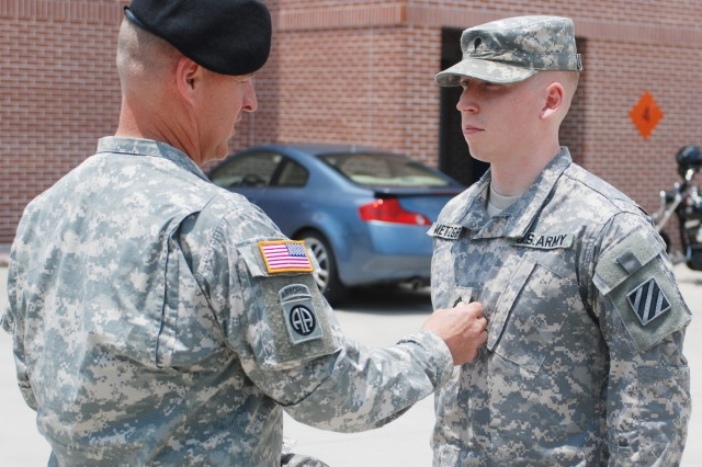 Command Sergeant Major Herbert Kirkover, left, brigade command sergeant major for the 1st Heavy Brigade Combat Team, 3rd ID, pins the sergeant rank onto Sgt. Sean Metzger, right, an avionics and armament technician with HHC, 3rd CAB, during a promotion ceremony June 14 at Hunter.