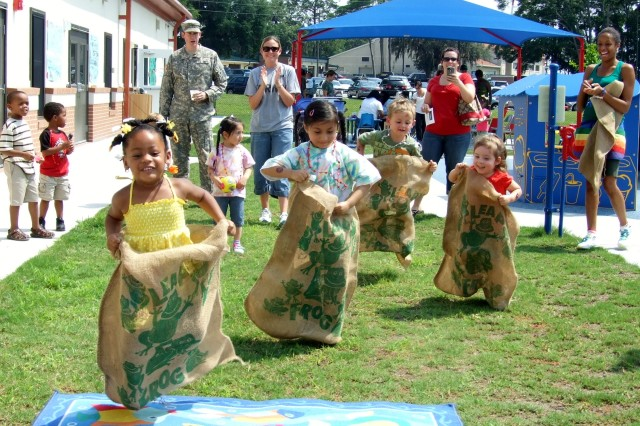 Teachers and parents cheer for pre-schoolers as they participate in a sack race, June 14, at the Child Development Center on Leonard-Neal Rd. to celebrate the Army's birthday.