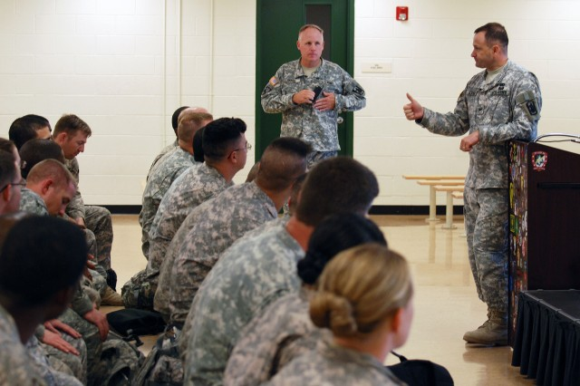 Col. Pierre Gervais (right), 470th Military Intelligence Brigade commander, briefs Soldiers of the 377th MI Battalion while the battalion commander stands by. Approximately 40 of the battalion's Soldiers deployed to Kuwait 10 months ago and returned to U.S. soil via Robert Gray Army Airfield, Fort Hood, Texas, June 14.  (U.S. Army photo by Gregory Ripps)