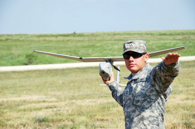 """Pvt. Patrick Hernandez, 1st Battalion, 5th Artillery Regeiment. 1st Heavy Brigade Combat Team, 1st Infantry Division, practices launching a RQ-11B Raven, June 12, 2012, at the Mock Airfield at Fort Riley, Kan. About 30 """"Big Red One"""" Soldiers received operator and master training courses from a mobile training team from Fort Benning, Ga."""