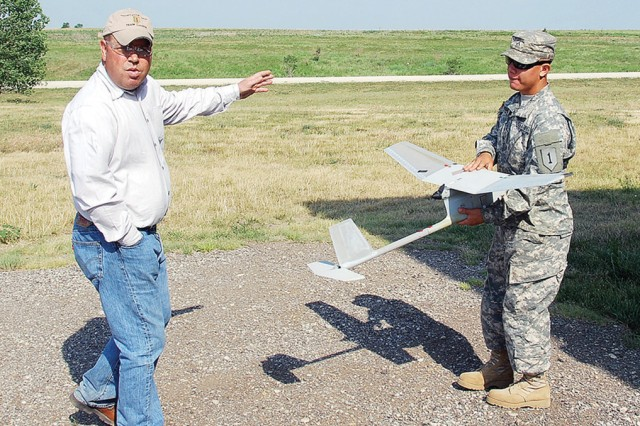 """Gary Smith, range liaison, Douthit Range Complex, Fort Riley DPTMS, left, introduces Pvt. Patrick Hernandez, 1st Battalion, 5th Artillery Regeiment. 1st Heavy Brigade Combat Team, 1st Infantry Division, right, to the Mock Airfield June 7, 2012, at Fort Riley, Kan. About 30 """"Big Red One"""" Soldiers took operator and master training courses in June from a mobile training team from Fort Benning, Ga., on the RQ-11B Raven, one of the smallest UAS used by the Army."""