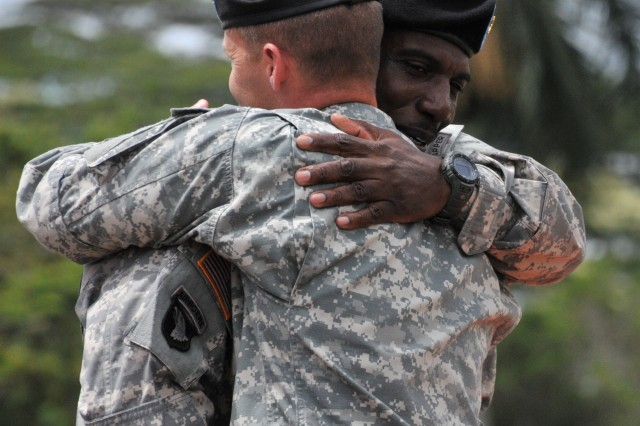 Col. Jeffrey Milhorn, brigade commander for the 130th Engineer Brigade, 8th Theater Sustainment Command, embraces outgoing command sergeant major, Command Sgt. Maj. Roy Ward, following his speech during the brigade's change of responsibility at Hamilton Field on Schofield Barracks, June 20.