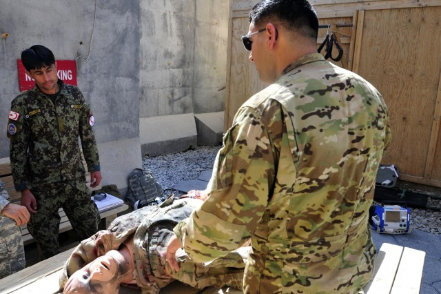 Staff Sgt. Miguel Valdez, a flight medic with Company C, 3rd Battalion, 25th Aviation Regiment, 25th Combat Aviation Brigade, teaches the basics of assessing a patient to Afghan National Army soldier Kushmal Muslimyar, a flight medic with the Kandahar Air Wing, during a training session on Kandahar Airfield, Afghanistan, June 19, 2012.