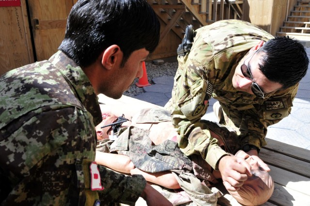 Staff Sgt. Miguel Valdez, a flight medic with Company C, 3rd Battalion, 25th Aviation Regiment, 25th Combat Aviation Brigade, instructs on signs to watch for while assessing a patient to Afghan National Army soldier Kushmal Muslimyar, a flight medic with the Kandahar Air Wing, during a training session on Kandahar Airfield, Afghanistan, June 19, 2012.