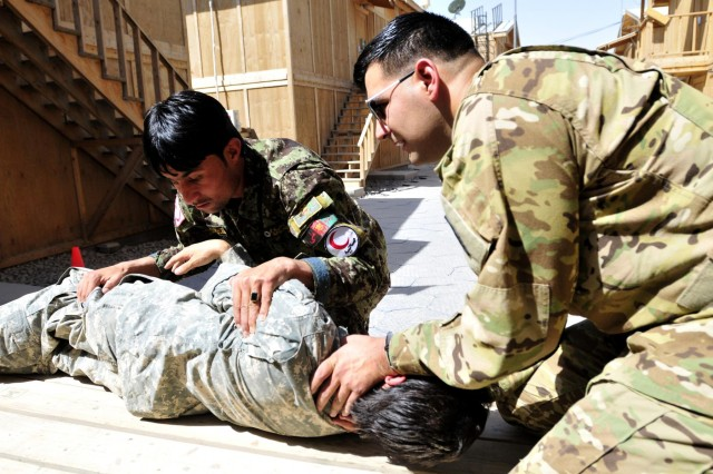 Afghan National Army soldier Kushmal Muslimyar, a flight medic with the Kandahar Air Wing, checks the back for an exit wound on a simulated casualty as part of his assessment of a patient during a training session with Staff Sgt. Miguel Valdez, a flight medic with Company C, 3rd Battalion, 25th Aviation Regiment, 25th Combat Aviation Brigade on Kandahar Airfield, Afghanistan, June 19, 2012.