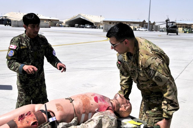 Afghan National Army soldier Kushmal Muslimyar, a flight medic with the Kandahar Air Wing, directs Staff Sgt. Miguel Valdez, a flight medic with Company C, 3rd Battalion, 25th Aviation Regiment, 25th Combat Aviation Brigade, on the proper way to load a patient onto a Medical Evacuation helicopter during a training session on Kandahar Airfield, Afghanistan, June 19, 2012.