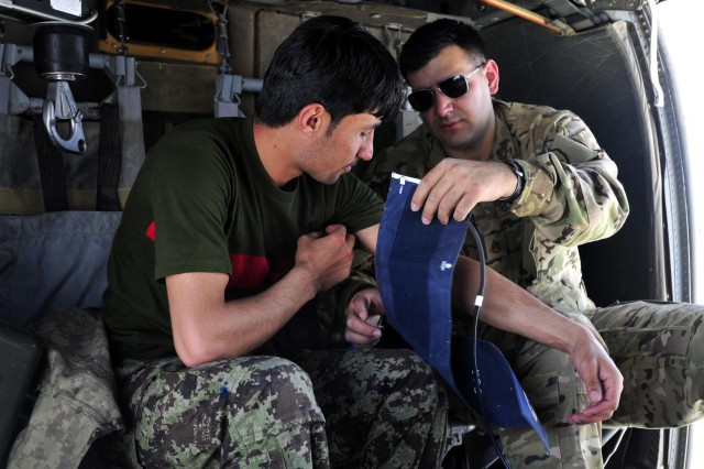 Staff Sergeant Miguel Valdez, a flight medic with Company C, 3rd Battalion, 25th Aviation Regiment, 25th Combat Aviation Brigade, demonstrates the proper way to measure blood pressure on Afghan National Army soldier Kushmal Muslimyar, a flight medic with the Kandahar Air Wing, during a training session in a UH-60 Black Hawk MEDEVAC helicopter on Kandahar Airfield, Afghanistan, June 19, 2012.