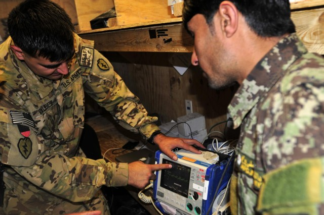 Staff Sergeant Miguel Valdez, a flight medic with Company C, 3rd Battalion, 25th Aviation Regiment, 25th Combat Aviation Brigade discusses defibrillator measurements with Afghan National Army soldier Kushmal Muslimyar, a flight medic with the Kandahar Air Wing, during a training session on Kandahar Airfield, Afghanistan, June 19, 2012.