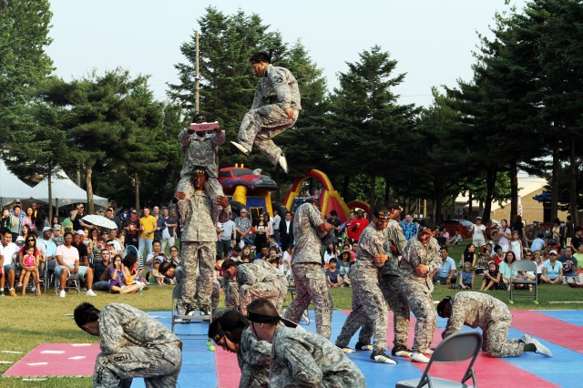 """At Camp Red Cloud June 14, Warrior Country celebrates the U.S. Army's 237th birthday with an outdoor party on the post's Village Green, an event to which the Army invited Korean residents of the Uijeongbu-Dongducheon region. Above, members of the 2nd Infantry Division's Taekwondo Team show off their high-flying talents before a crowd of spectators. """" U.S. Army photo by Sgt. 1st Class Jeff Troth"""
