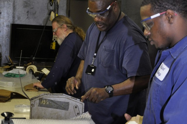 From right to left, Sean Stephenson, Kevin Chase, and Frank Collins work late in the afternoon on a small assembly line that was for a recent non-core mission, parts for the Stryker vehicle gunner restraint system.