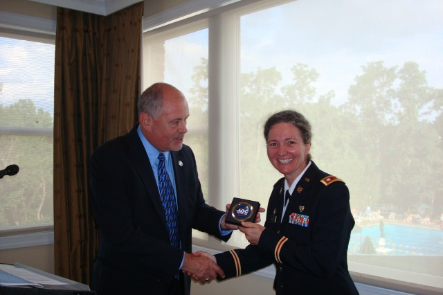 Lt. Col. Lisa Mahood accepts a token of appreciation for speaking at the Capital Club townhall meeting in Alexandria, Va., from the Capital Club Chapter President Geoff Leighton, June 15, 2012.