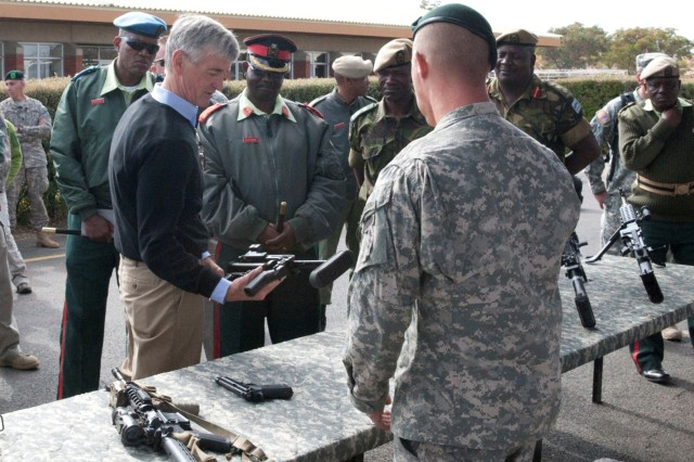 Secretary of the Army John McHugh lifts a weapon used during a capabilities demonstration to check its weight as a U.S. Army Special Forces Soldier responds to his questions following a capabilities demonstration by Botswana Defence Force soldiers during Exercise Eastern Piper 2012, near Gaborone, Botswana, June 20, 2012.