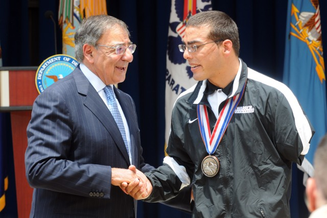 Secretary of Defense Leon E. Panetta presented his coin to Staff Sgt. Michael Kacer, now retired, during the Department of Defense Warrior Games Recognition Ceremony, June 25, 2012, in the Pentagon Courtyard.  Kacer participated in the recent 2012 Warrior Games in Colorado Springs, Colo.  He was one of ten Soldiers asked to represent all Army participants of those games at the Pentagon ceremony.