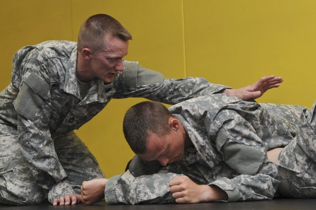 Sgt. 1st Class Adam McQuiston, from Fort Leonard Wood, Mo., directs two Soldiers on the proper way to perform a combatives move, June 25, 2012, during the annual Drill Sergeant of the Year competition hosted by Initial Military Training, U.S. Army Training and Doctrine Command at Fort Eustis, Va. McQuiston is one of six drill sergeants competing in this week-long competition for the title.
