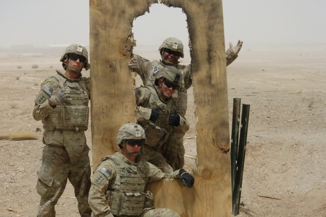 (Left to right) Sgt. Christopher Weiss, Sgt. Bradley Tilfas, Pfc. Kevin Pons, and Pfc. Joesph Huckaby pose with a door that was breached using a silhouette charge. Demolition ranges are not only a great training exercise for the combat engineers, but they are also an effective way to unwind between route clearance missions.
