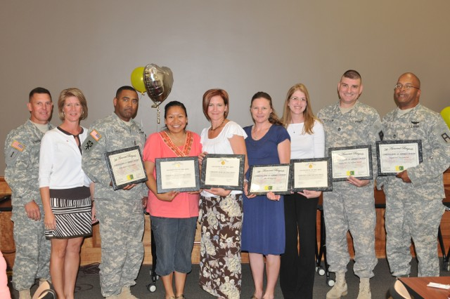 Col. Eric Schacht, left, commander of 5th Armored Brigade, Division West, poses with Soldiers and spouses at an awards ceremony during the unit's Family Readiness Group Conference held recently at Fort Bliss, Texas. Also pictured are, left to right, Amy Schacht, Master Sgt. Terrence Sargeant, Loralee Cantrell, Heidi Kokes, Michaela Dorf, Heather Peterson, Sgt. 1st Class William Peterson and Sgt. 1st Class Kevin Earl. Kokes, Contrell and Peterson received awards for exceptional public service; the rest received certificates of achievement from the brigade. (Photo by Sgt. Richard Hernandez, 402nd Field Artillery Brigade, Division West, Public Affairs)