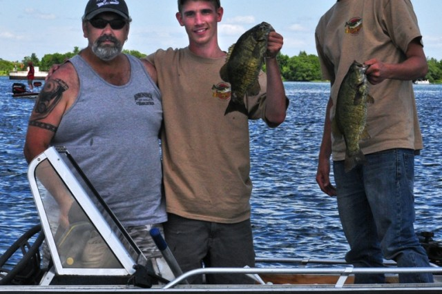Spc. Robert Knights (center), Company C, 4th Battalion, 31st Infantry Regiment, 2nd Brigade Combat Team, 10th Mountain Division, and his younger brother, Eugene Fitzsimmons (right), proudly hold up their catch as their team boat captain looks on at the Wounded Warrior Bass Derby, June 23.