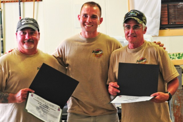 Capt. Jayson Williams (center), commander of Headquarters and Headquarters Company, 2nd Battalion, 87th Infantry Regiment, 3rd Brigade Combat Team, 10th Mountain Division, presents certificates of appreciation to Bob Giordano and Don Meissner, who served as coordinators for the Wounded Warrior Bass Derby, June 23, in Ogdensburg.