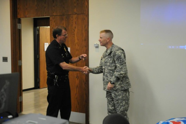 "Col. Patrick D. Frank, commander of the 3rd Infantry Brigade Combat Team, 10th Mountain Division, presents Watertown, N.Y. Police Chief, Joseph Goss, with the ""Shona ba Shona"" Medal during a briefing at Watertown City Hall, June 8.   ""Shona ba Shona"" means ""shoulder to shoulder"" in Pashtu and became the brigade's motto during their deployment as they stood ""shona ba shona"" with the Afghan National Security Forces."