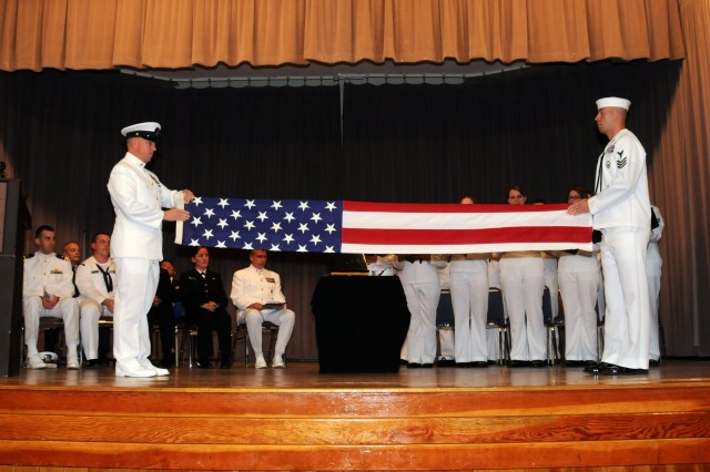 PRESIDIO OF MONTEREY, Calif. - Chief Petty Officer Christopher Washburn and Petty Officer 1st Class Caleb Walser ceremoniously fold the national ensign during a memorial ceremony for Boatswain's Mate 2nd Class Jason Steen, who died unexpectedly while camping May 19.