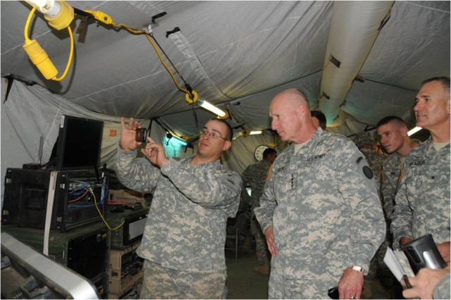 A Soldier from A Company 1/35th Armored Battalion, 2nd Brigade Combat Team, 1st Armored Division, demonstrates an application he designed to Gen. Robert W. Cone, commander of U.S. Army Training and Doctrine Command, during Network Integration Evaluation 11.2 in June 2011.
