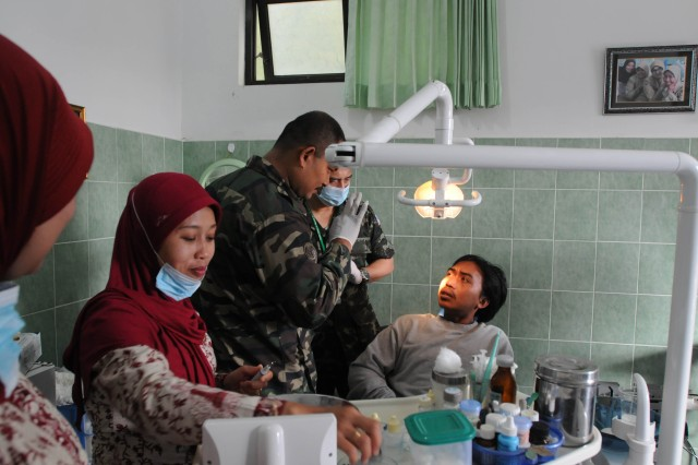 Malaysian army dentists and health care providers exam a gentleman while an at a medical clinic in Malang Indonesia in which health providers from the United States, Indonesia, Australia, Cambodia, Malaysia, Nepal, Philippines, Thailand, Timor Leste, Tonga and Vietnam were giving aid to families as one of the events during Exercise Tendon Valiant 2012 a six day multi-national Medical Readiness Training Exercise, led by 18th Medical Command (Deployment Support), and US Army Pacific, Surgeon's office  and hosted by the Indonesian National Armed Forces - Tentara National Indonesia 18-23 June.