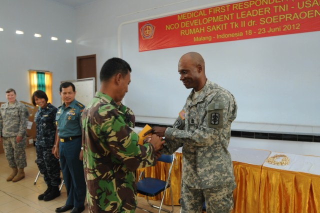 Command Sgt. Maj. Garfield Skyers, 18th Medical Command (Deployment Support), congratulates and provides a manual for a member of the Indonesian army, at the closing ceremony for the Medical First Responder course for health care specialist officers and non-commissioned officers of the Indonesian Army, one of the events during Exercise Tendon Valiant 2012 a six day multi-national Medical Readiness Training Exercise, led by 18th Medical Command (Deployment Support), and US Army Pacific, Surgeon's office  and hosted by the Indonesian National Armed Forces - Tentara National Indonesia 18-23 June.