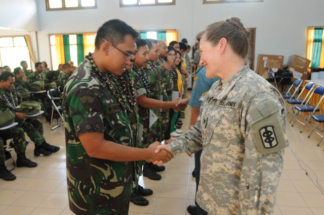 Col. Judith Bock, commander, 18th Medical Command (Deployment Support), congratulates Dr. (Cpt.) Nursito, marine, Indonsian army, at the closing ceremony for the Medical First Responder course for health care specialist officers and non-commissioned officers of the Indonesian Army, one of the events during Exercise Tendon Valiant 2012 a six day multi-national Medical Readiness Training Exercise, led by 18th Medical Command (Deployment Support), and US Army Pacific, Surgeon's office  and hosted by the Indonesian National Armed Forces - Tentara National Indonesia 18-23 June.