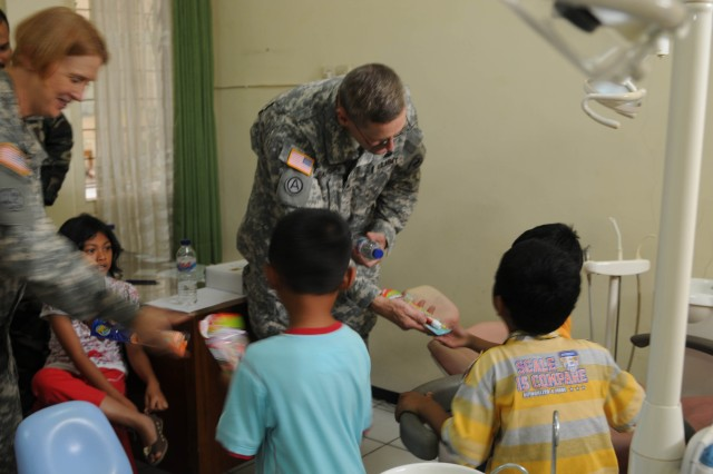 Lt. Col. Lillian Landrigan, dental surgeon, 18th Medical Command (Deployment Support), and Brig. Gen. Keith Gallagher, commander, U. S. Army Pacific Surgeon, give children dental hygiene items at a medical clinic in Malang Indonesia in which health providers from the United States, Indonesia, Australia, Cambodia, Malaysia, Nepal, Philippines, Thailand, Timor Leste, Tonga and Vietnam were giving aid to families as one of the events during Exercise Tendon Valiant 2012 a six day multi-national Medical Readiness Training Exercise, led by 18th Medical Command (Deployment Support), and US Army Pacific, Surgeon's office  and hosted by the Indonesian National Armed Forces - Tentara National Indonesia 18-23 June.