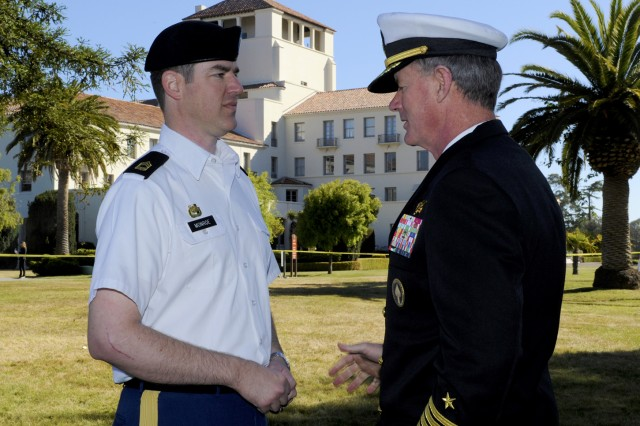 Naval Postgraduate School Defense Analysis student Master Sgt. Jim Monroe, left, is congratulated on his selection as the quarter's top Army student by Commander of the U.S. Special Operations Command, Adm. William McRaven, during a campus visit, June 7, 2012. McRaven is also an NPS graduate, receiving dual master's degrees in 1993.