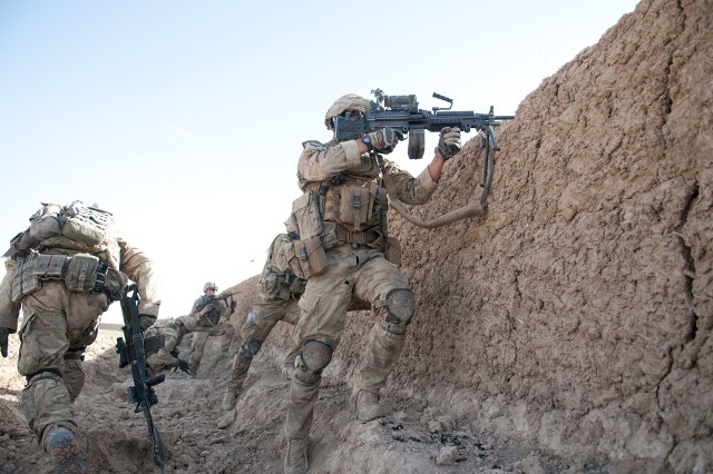 A paratrooper with the 82nd Airborne Division's 1st Brigade Combat Team fires his M249 squad automatic weapon at insurgents during a firefight in Afghanistan's southern Ghazni Province, June 15, 2012.