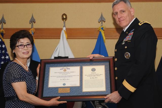 Kim Je-gwon (left), the daughter of train enginner Kim Jae-hyun, receives the Exceptional Civilian Service Award from Lt. Gen. John D. Johnson, June 26, 2012, at Yongsan Garrison, South Korea.