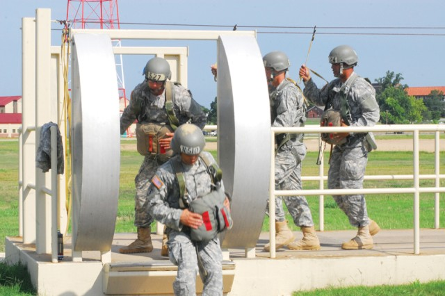 Soldiers prepare for a 34-foot leap by ocnducting a mass exit from a mock door on Eubanks Field.