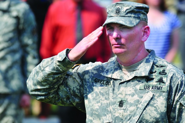 "Fort Belvoir's Command Sgt. Maj. Chester Grelock, holds a salute as ""The Star-Spangled Banner"" is played during Fort Belvoir's change of command ceremony, June 25."