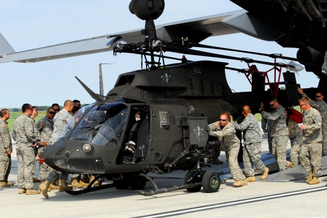 Soldiers from the 1st Infantry Division's Combat Aviation Brigade unload a OH-58 Kiowa Warrior from an Air Force C-17 Globemaster during an emergency deployment readiness exercise June 23 at Marshall Army Airfield on Fort Riley.