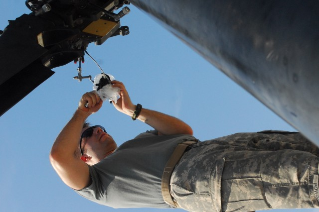 """A Soldier from the 1st Infantry Division's Combat Aviation Brigade places the blades back on an aircraft June 23 during the brigade's emergency deployment readiness exercise. More than 100 Soldiers from the """"Demon"""" brigade joined Air Force crewmembers for the week-long exercise."""