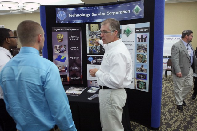 Alan Hislop, Technology Services Corporation-PIVC, explains his booth as attendees pause at his exhibit. Hislop was one of 18 exhibitors at the 2012 Letterkenny Business Opportunity Showcase.